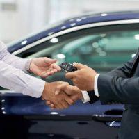 Salesman giving car keys to customer and shaking his hand