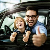 Happy single father and son testing new car in a showroom and showing thumbs up.